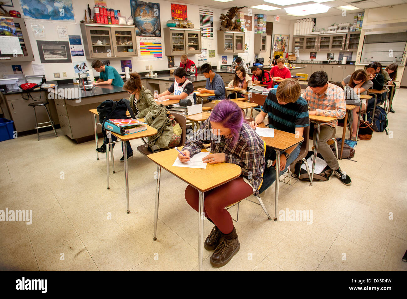 Teen high school chemistry students taking a classroom examination in San Clemente, CA. Note purple hair. - Stock Image