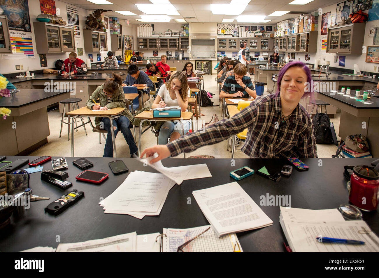 A high school chemistry student in San Clemente, CA, turns in her exam paper. Note cell phones placed on desk to avoid distraction. - Stock Image