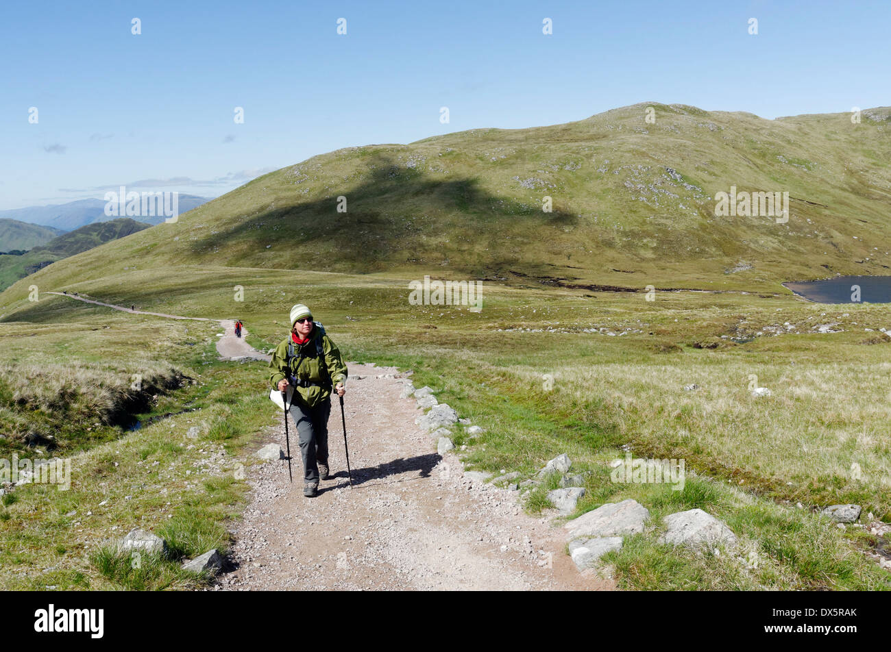 A lady hillwalker passing the Halfway Lochan on the CMD arete route on Ben Nevis in the Scottish Highlands - Stock Image