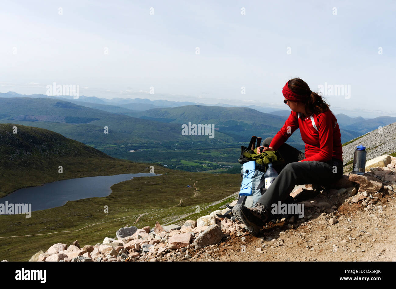 A lady hillwalker takes a break on the ascent of Ben Nevis with the Halfway Lochan below - Stock Image