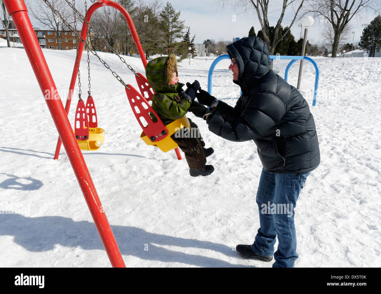A mother and child playing on the swings in a park in Quebec in mid winter. It was -16C. - Stock Image