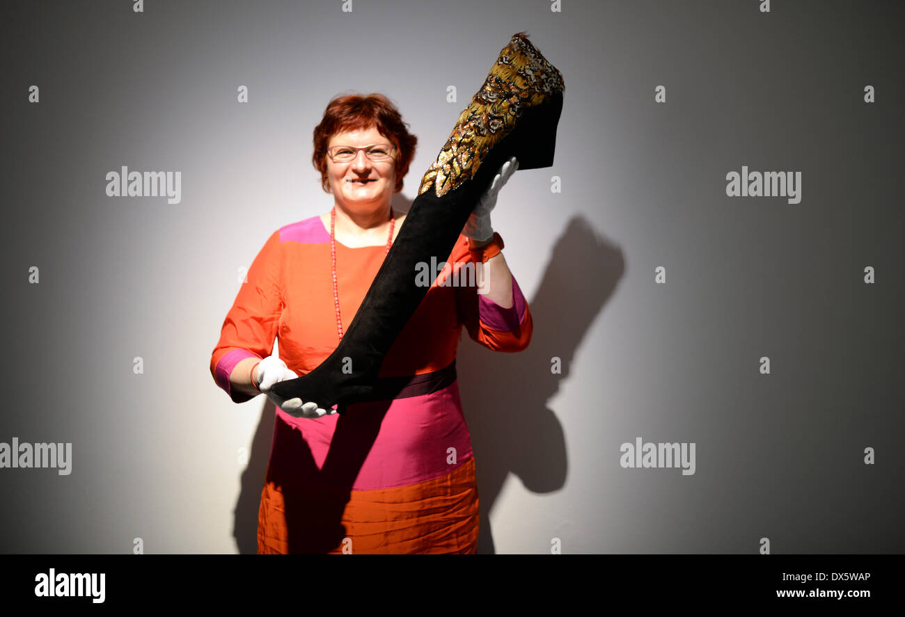 Offenbach, Germany. 18th Mar, 2014. Curator Rosita Nenno shows a boot from 1987 in the exhibition 'Roger Vivier: SchuhWERKE' in the International Leather Museum in Offenbach, Germany, 18 March 2014. Shoes of designer Roger Vivier, the inventor of the stiletto heel, are exhibited in Offenbach from 22 March to 02 November 2014. Photo: Daniel Reinhardt/dpa/Alamy Live News - Stock Image