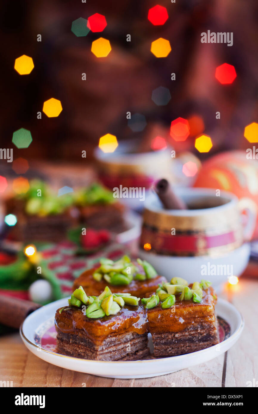 Traditional german christmas multi-layered cake with pistachio and cup of coffee - Stock Image