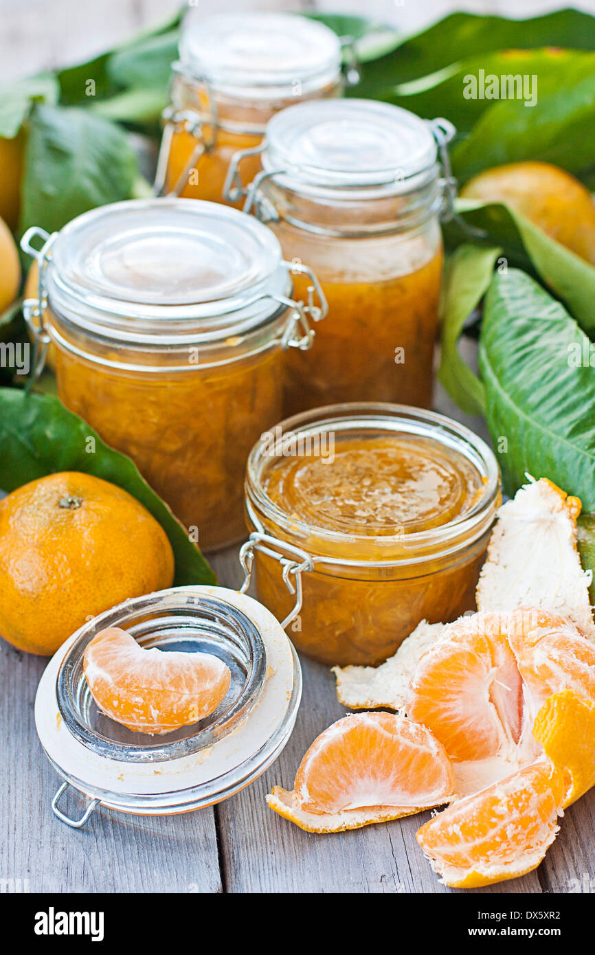 Various jars with homemade mandarine jam on old wood table - Stock Image