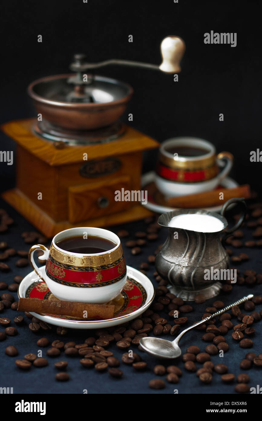 Two cups of coffee with copper coffee mill and silver milk jug - Stock Image