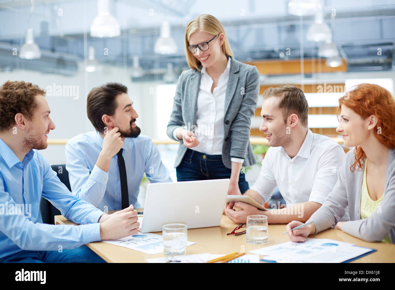 Close-knit business team approving his colleague's idea about company's development - Stock Image