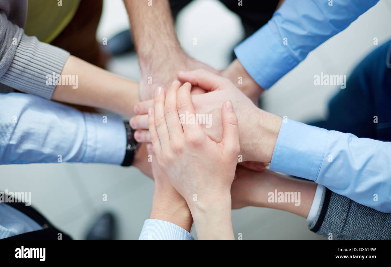 Above view of business partners making a pile of hands - Stock Image