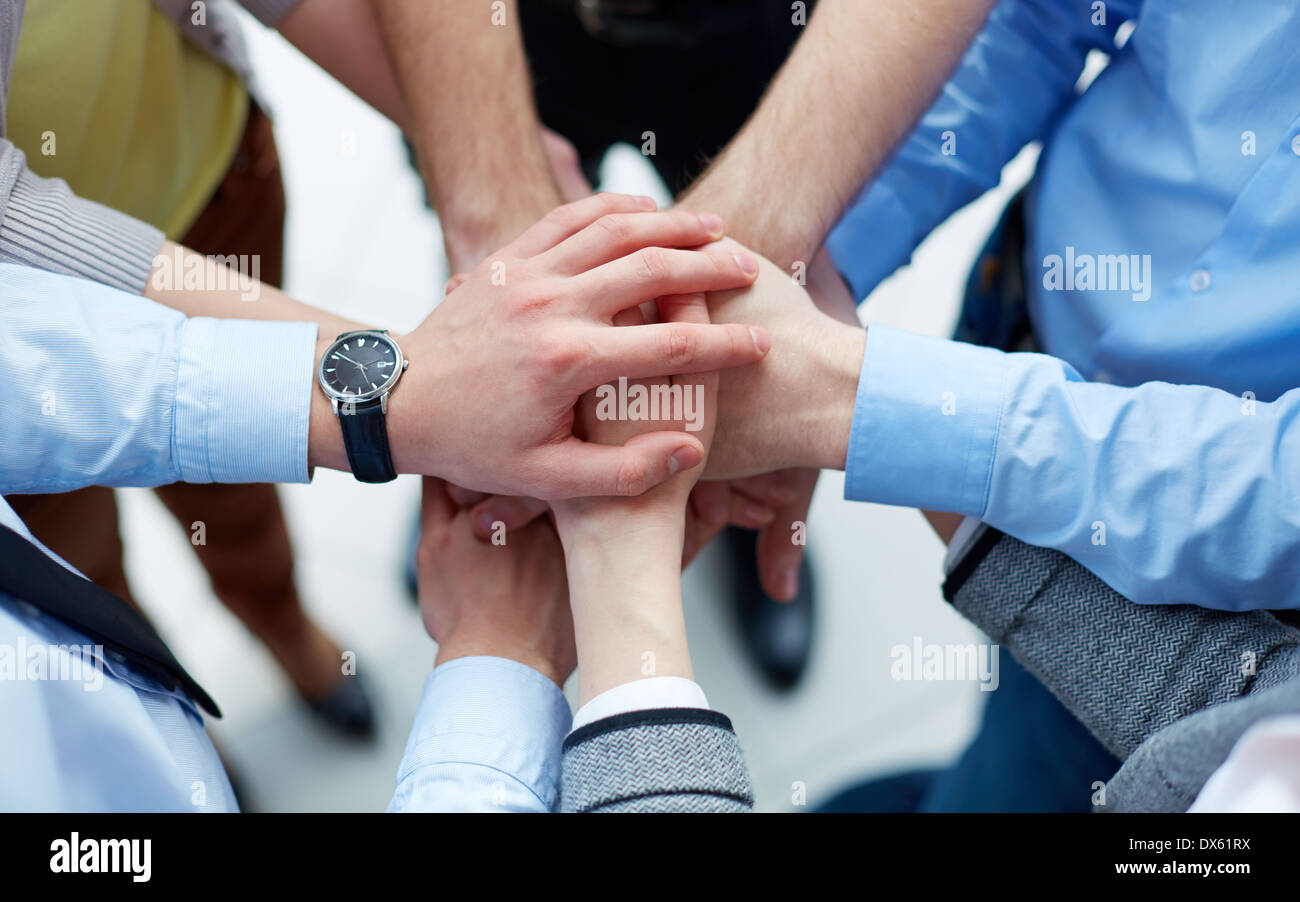 Businesspeople joining their hands in the sign of unity - Stock Image