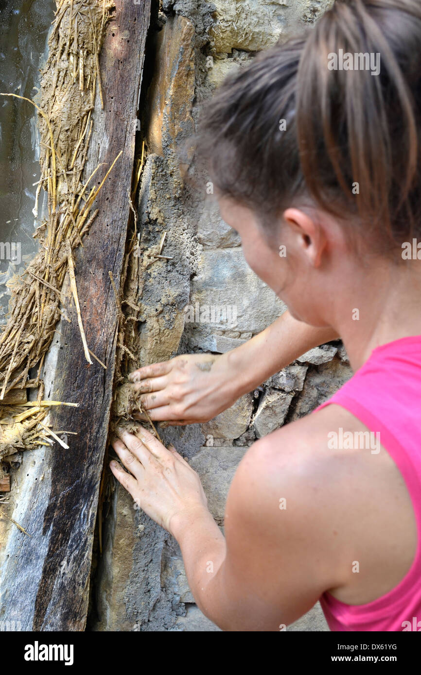 Young female plastering a old stone building with natural materials - clay, sand and straw. Stock Photo