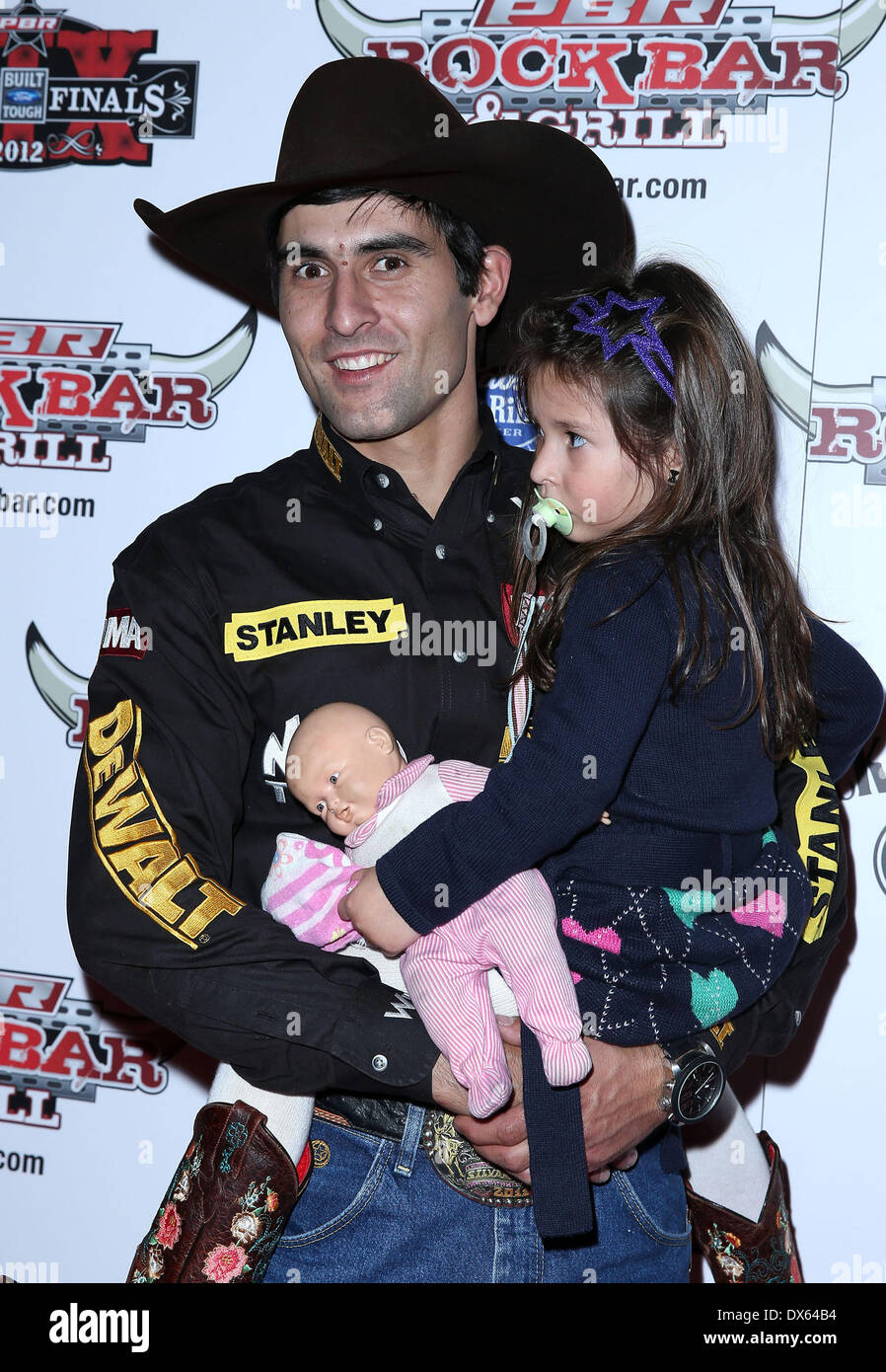 Silvano Alves and daughter Professional Bull Rider Superstars walk the red carpet at PBR Rock Bar inside The Miracle Mile Shops at Planet Hollywood Resort and Casino Las Vegas, Nevada - 26.10.12 Featuring: Silvano Alves and daughter Where: United States When: 26 Oct 2012 - Stock Image