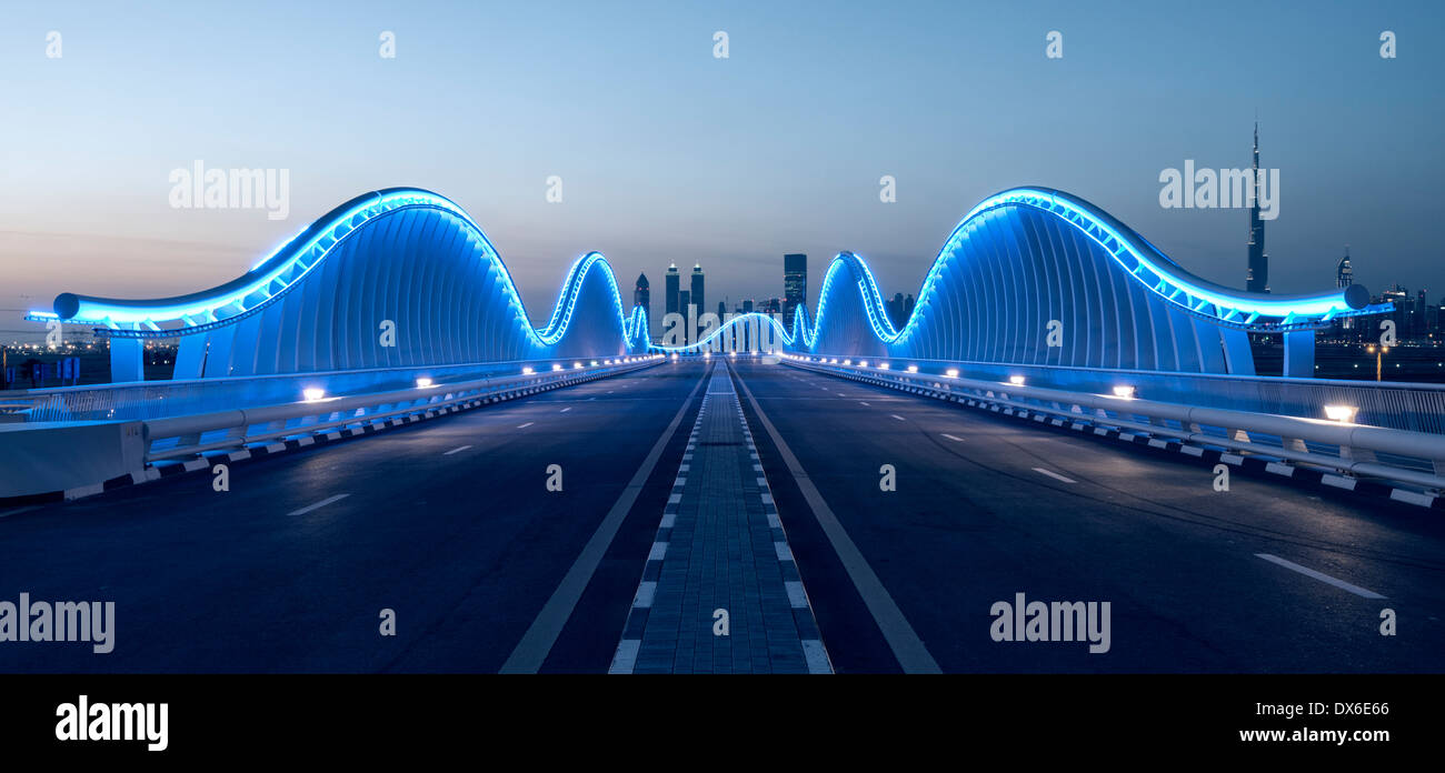 Modern architectural illuminated bridge at Meydan racecourse in Dubai United Arab Emirates - Stock Image