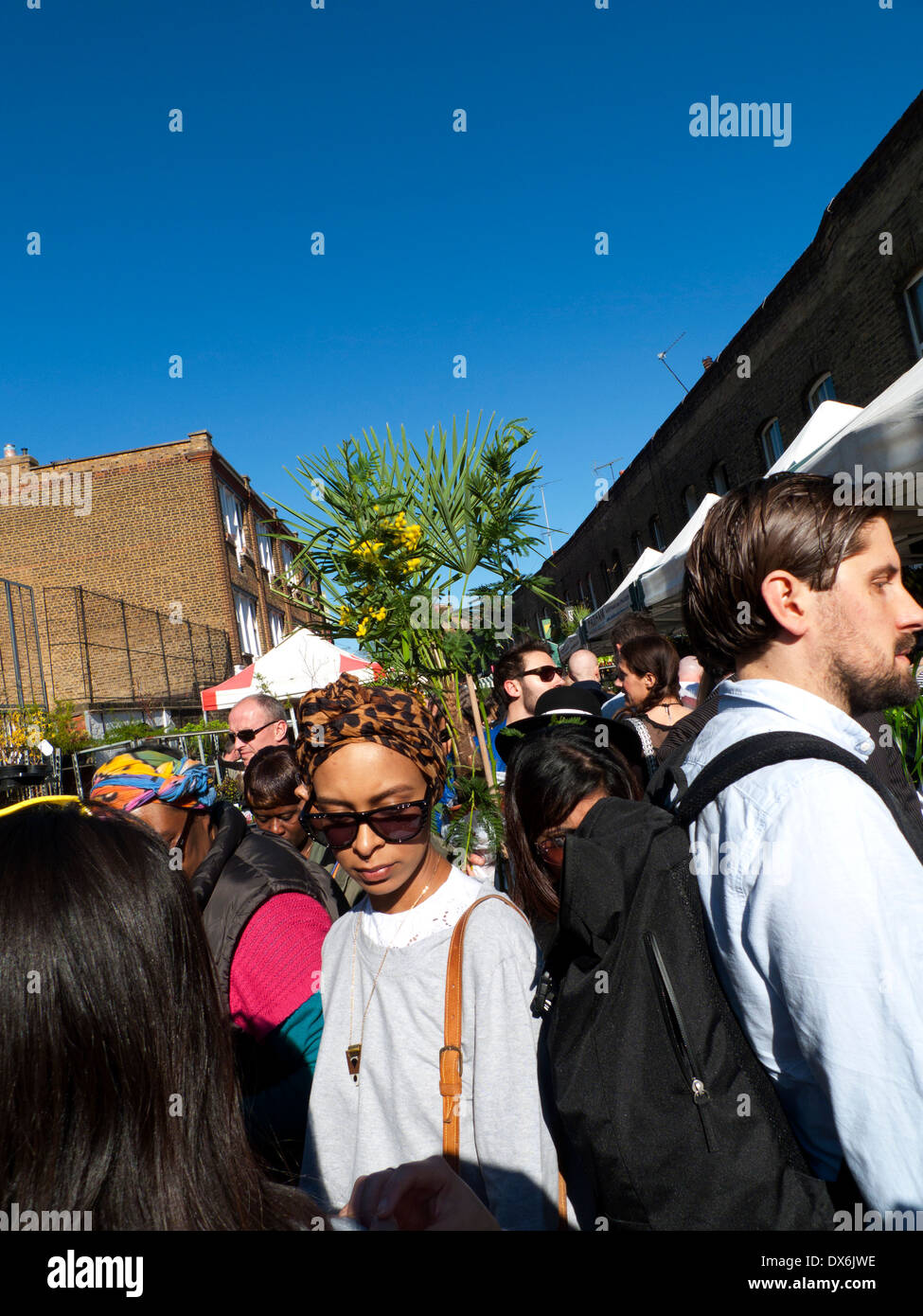 An attractive young woman makes her way through the crowd at Columbia Road Flower Market London E2 England UK  KATHY DEWITT - Stock Image
