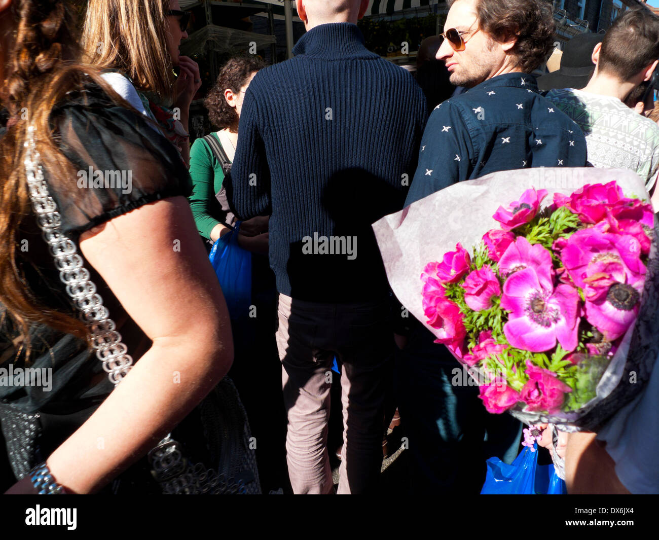 Pink anenome cut flowers in the crowded street at Columbia Road Flower Market London E2 England UK  KATHY DEWITT - Stock Image