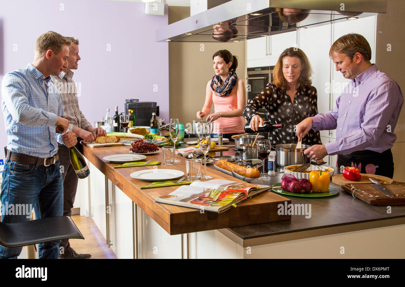Friends Cooking Together In A Kitchen Preparing A Meal