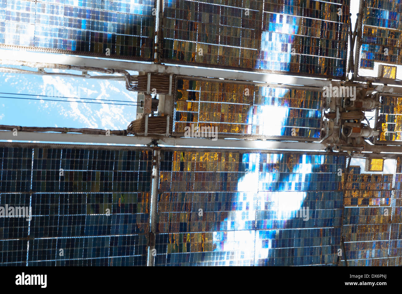 This close-up picture of a Zvezda Service Module array of the International Space Station, reflecting bright rays of the sun - Stock Image