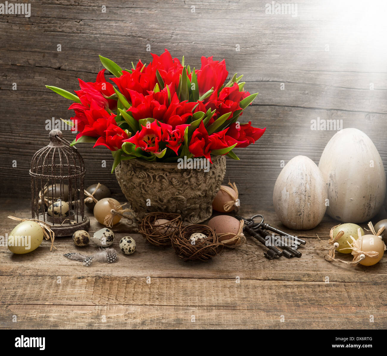 vintage easter composition with eggs and red tulips. nostalgic still life home interior with light beams Stock Photo