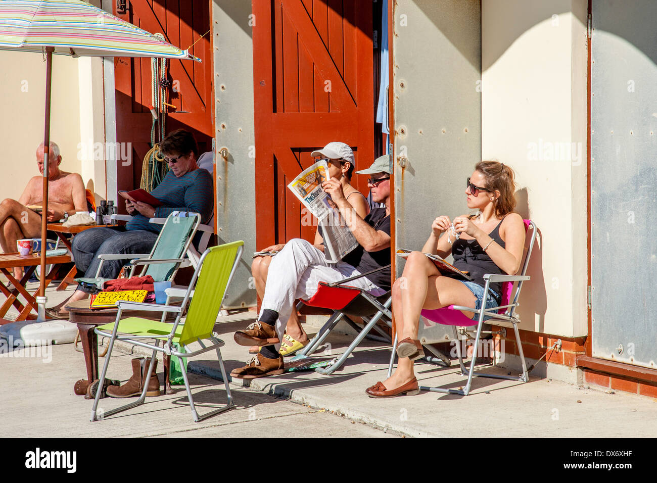 People Relaxing Outside Beach Huts, Rottingdean, Sussex, England - Stock Image