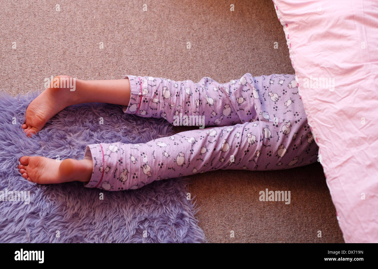 Young girl searching underneath her bed. - Stock Image
