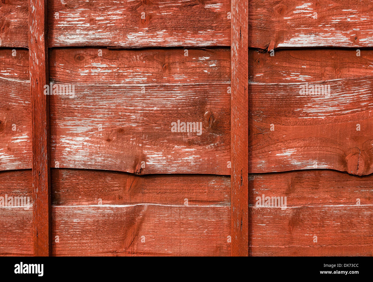 Red stained, rough wood fence panel; medium close, landscape orientation. - Stock Image