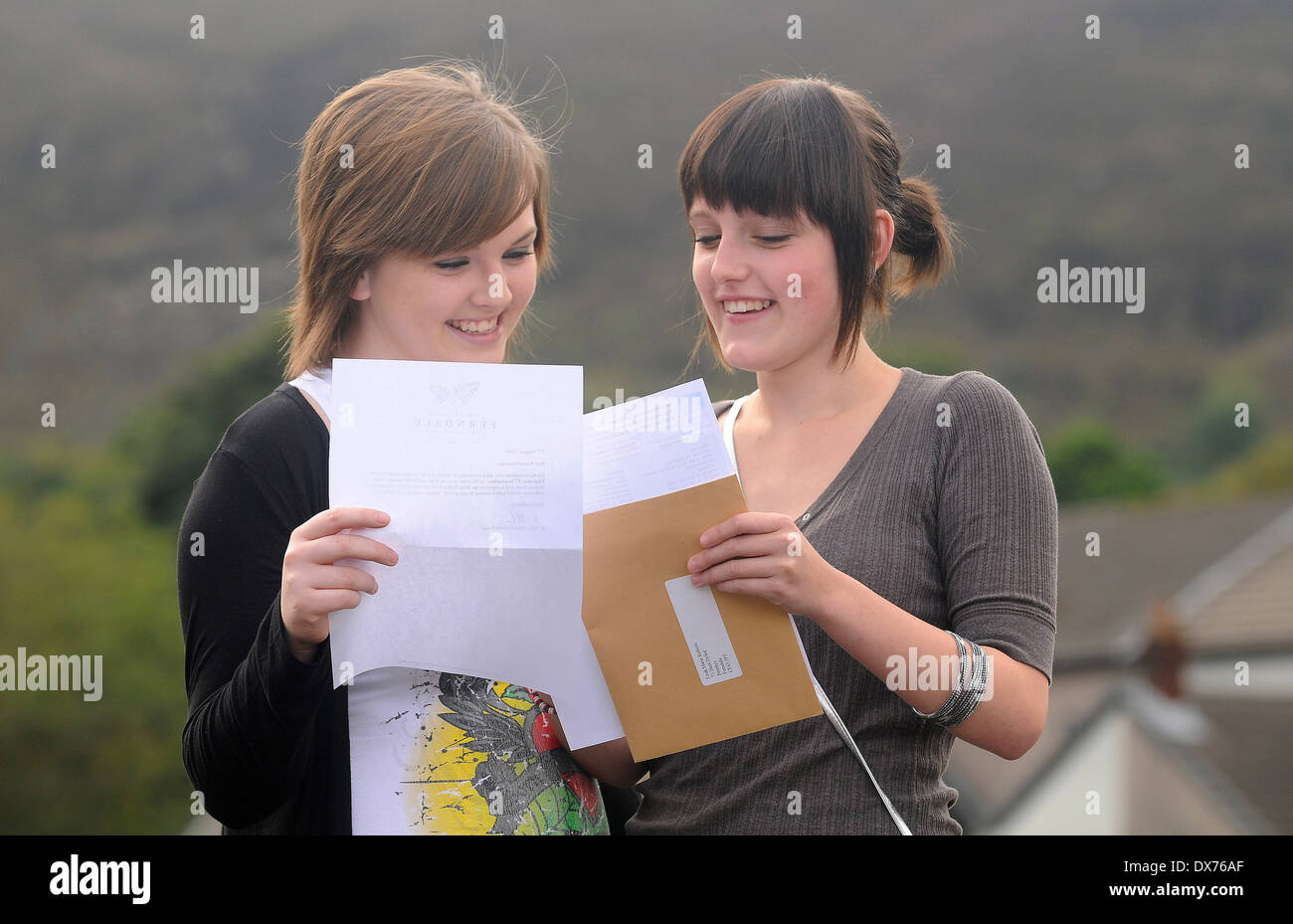 Students open their GCSE results on results day. - Stock Image
