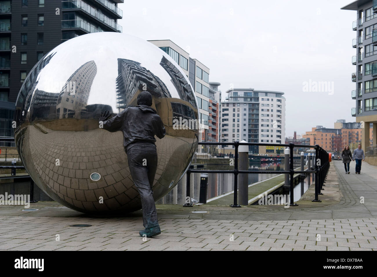 Sculpture in New Dock, formerly Clarence Dock, Leeds, showing life size bronze figure pushing a stainless steel ball. - Stock Image