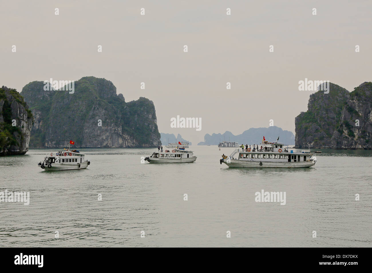 Tour boats in Ha Long Bay surrounded by  limestone karst formations.  Vietnam,Southeast Asia Stock Photo