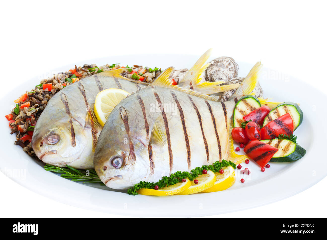 Grilled Pompano fish with wild rice ,vegetables and oysters on a white background. - Stock Image