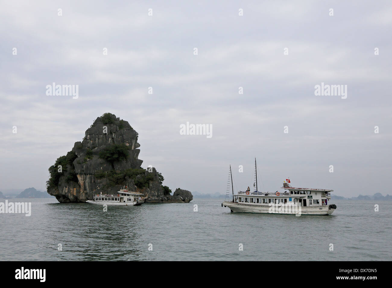 Tour boats in Ha Long Bay surrounded by  limestone karst formations.  Vietnam, Southeast Asia - Stock Image