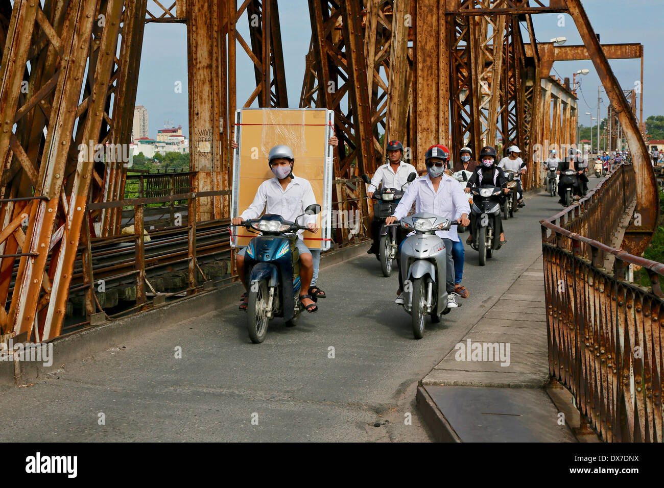 Motorcycles cross the Long Bien Bridge to Hanoi. The bridge which spans the Red River is 1682 m long and opened in 1903. - Stock Image