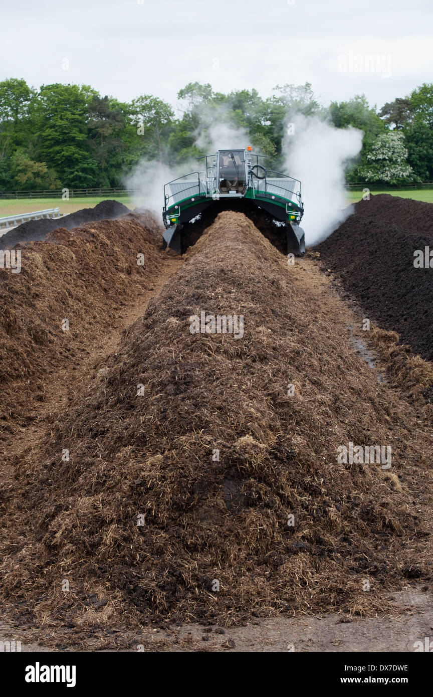Komptech self propelled compost turner, turning over rotting bedding manure. - Stock Image