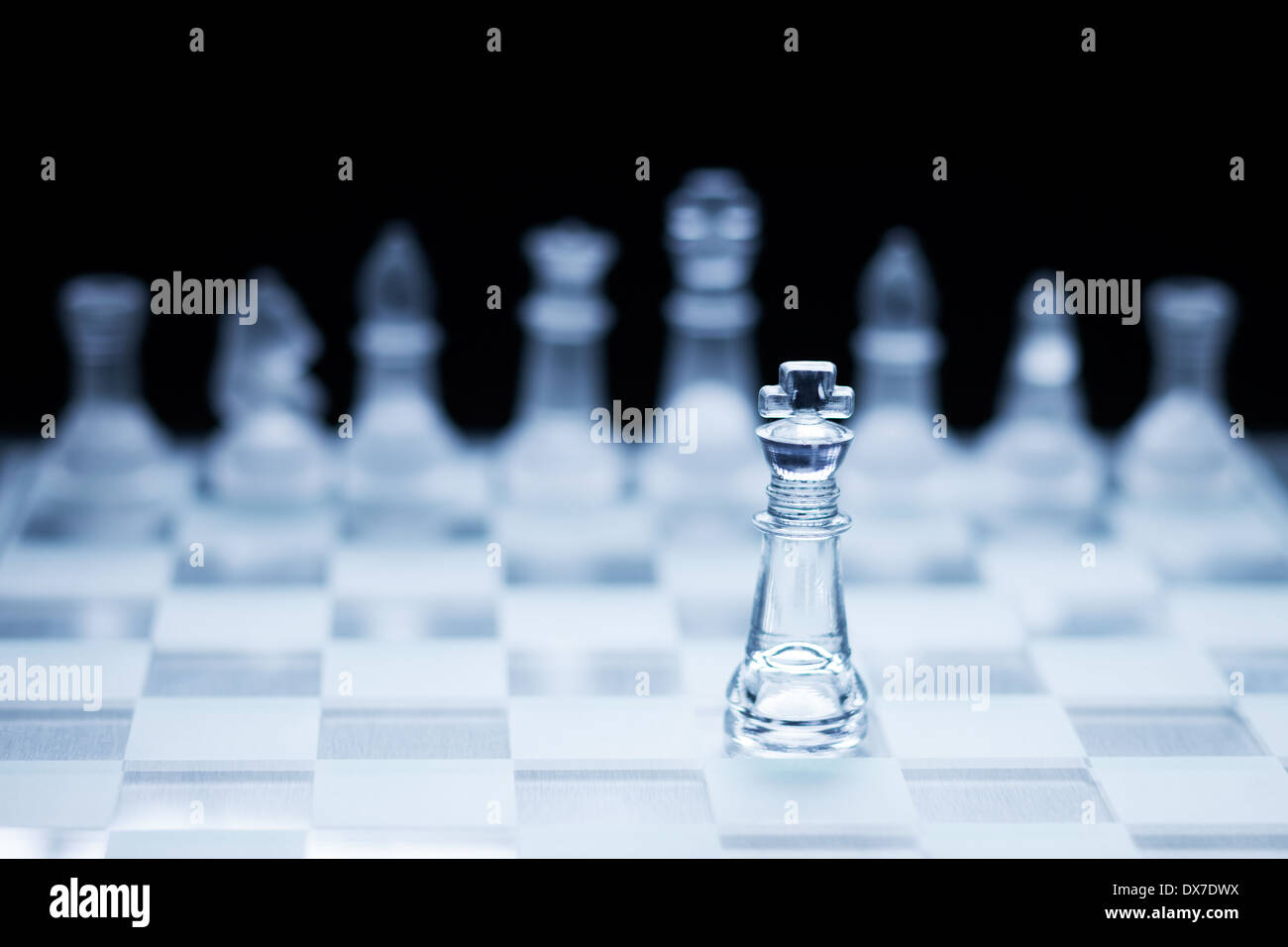 Photo of chess king standing in front of the other colour set in bright background. - Stock Image