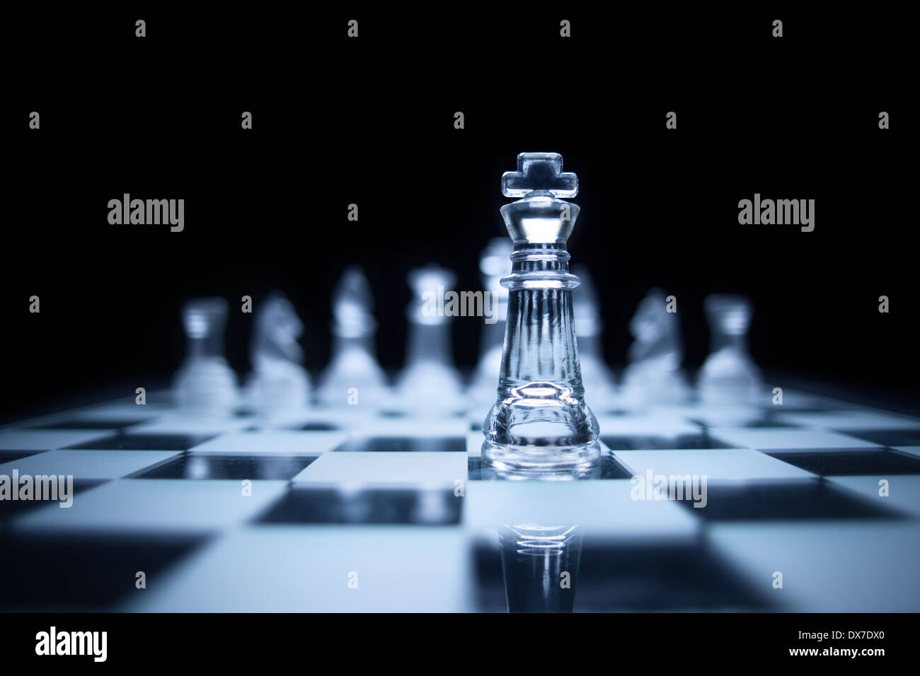 Photo of chess king standing in front of the same colour set in black background. - Stock Image
