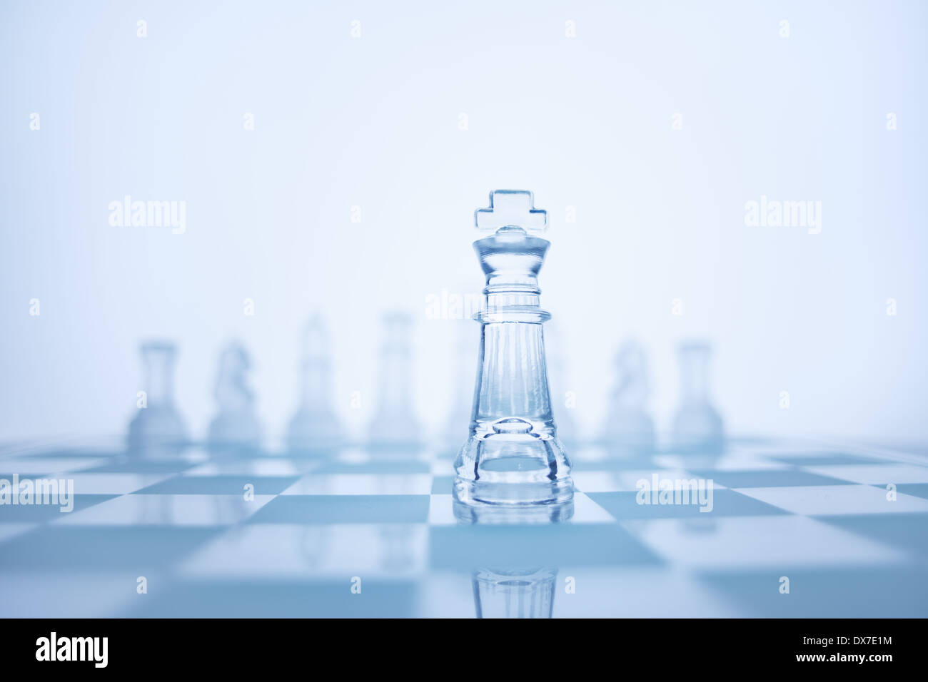 Photo of chess king standing in front of the same colour set in bright background. - Stock Image