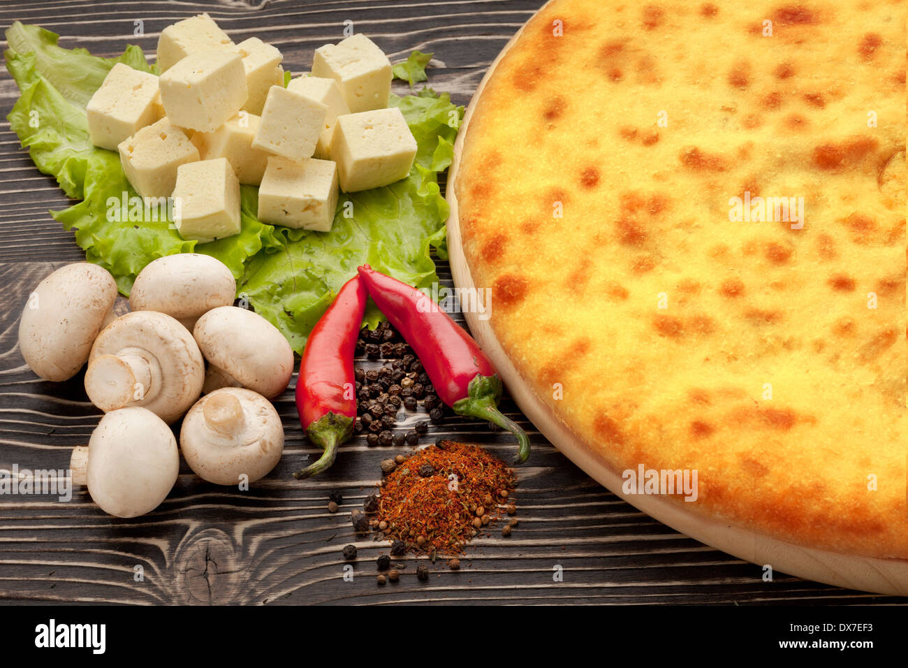 Ossetian cuisine. Kozodjin meat pie and vegetables on wood. - Stock Image