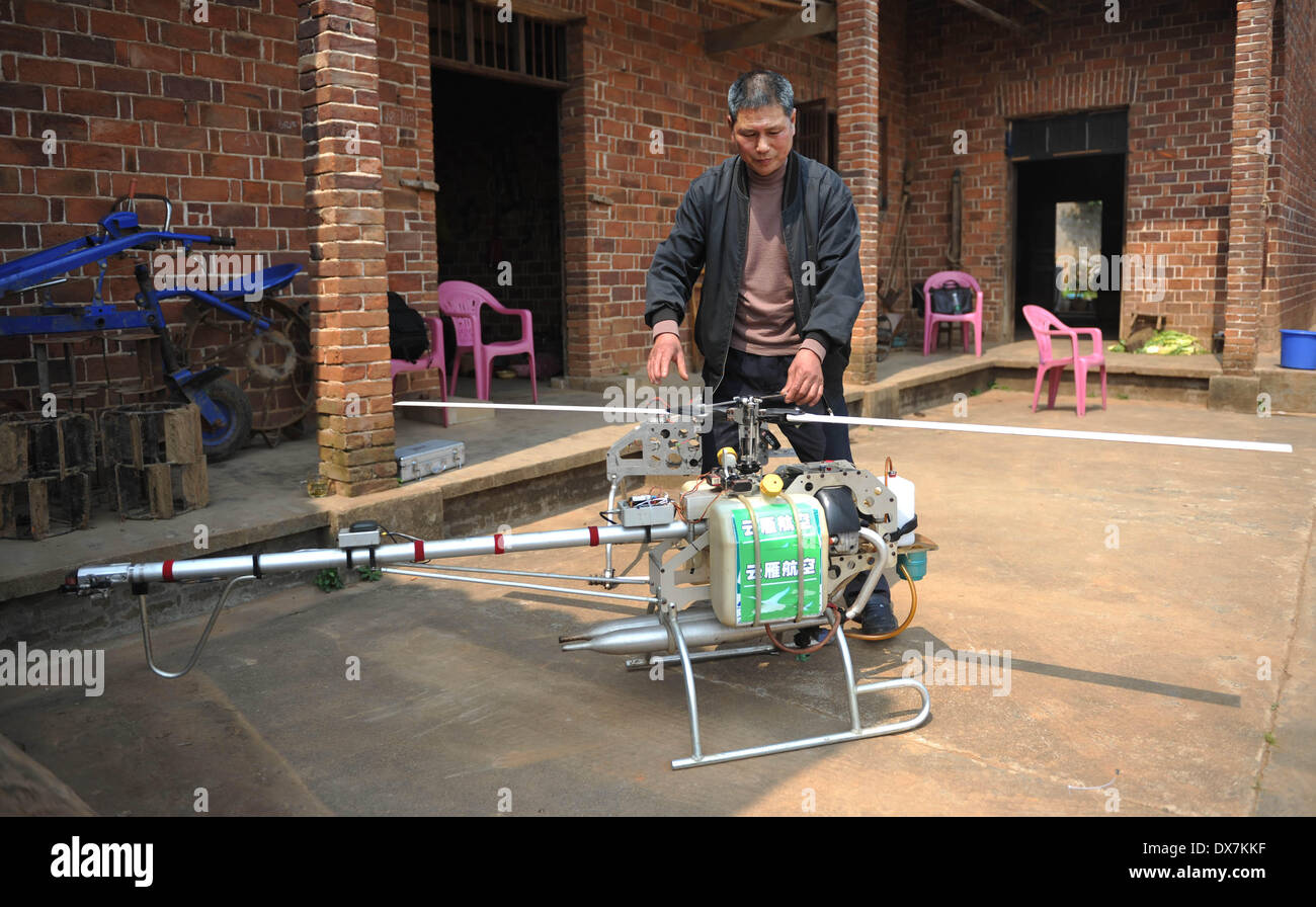 (140320) -- CHANGSHA, March 20, 2014 (Xinhua) -- Zhang Aiguo adjusts the propeller of a self-made drone in his yard in Xiangtan County, central China's Hunan province, March 18, 2014. Zhang Aiguo, 62, a farmer from central China's Hunan province, has made 5 farming drones with his partners since 2013, which cost just less than 20,000 dollars for each one. The aircraft enthusiast made his specifically designed drones by inviting professionals to do the designs, buying imported engines online and ordering body frames from aircraft factories. Moreover, Zhang used lighter materials to save weigh - Stock Image