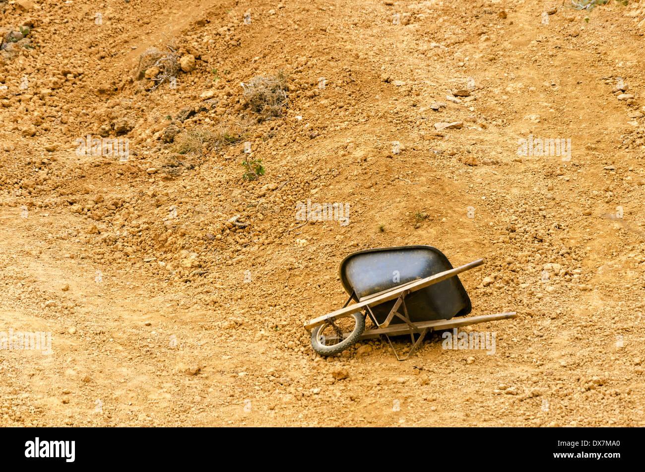 Black wheelbarrow in a dry barren setting - Stock Image