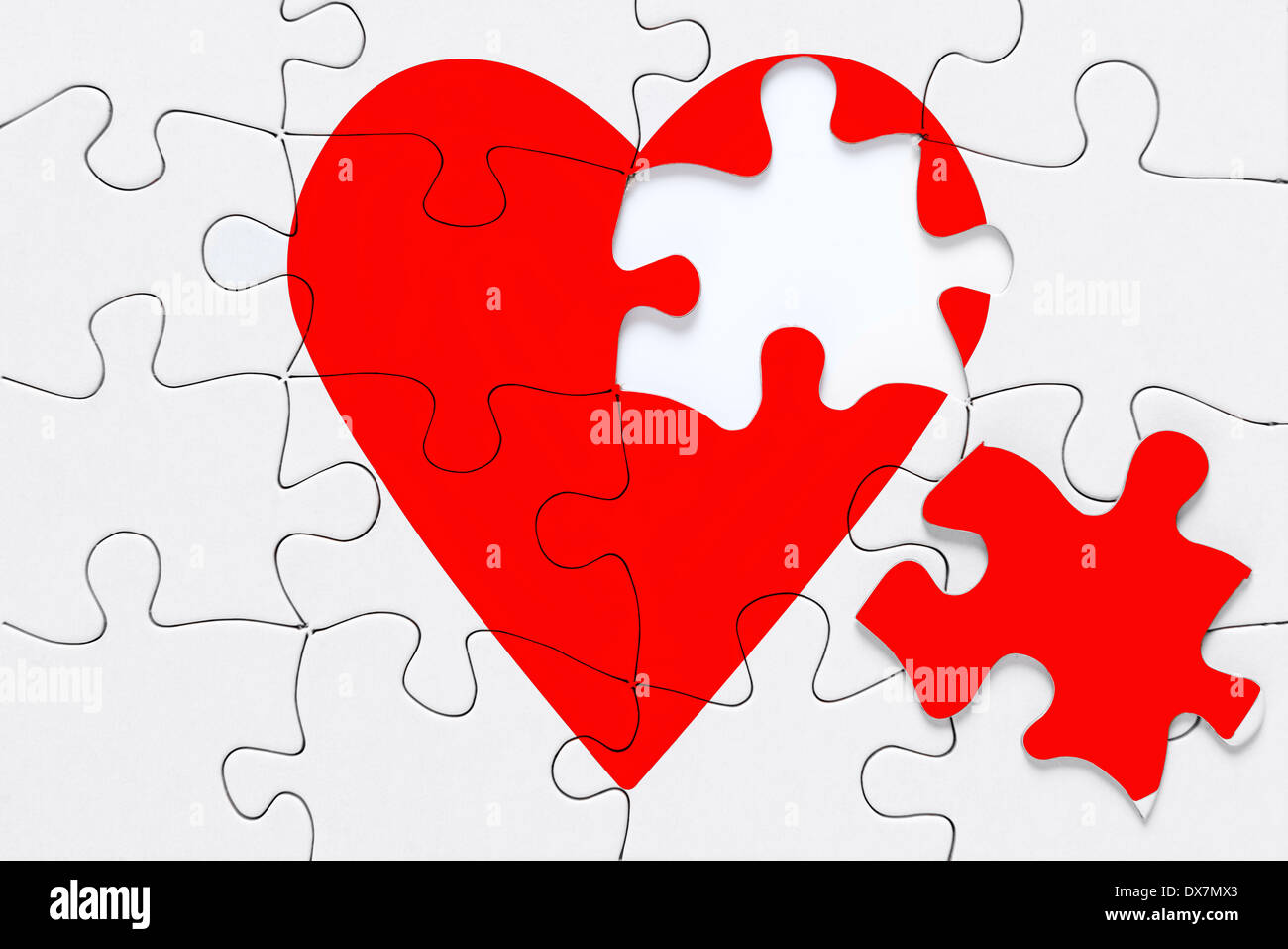 A red heart jigsaw puzzle with a piece on the side, good image for a broken heart, love, romance and Valentine themes. - Stock Image