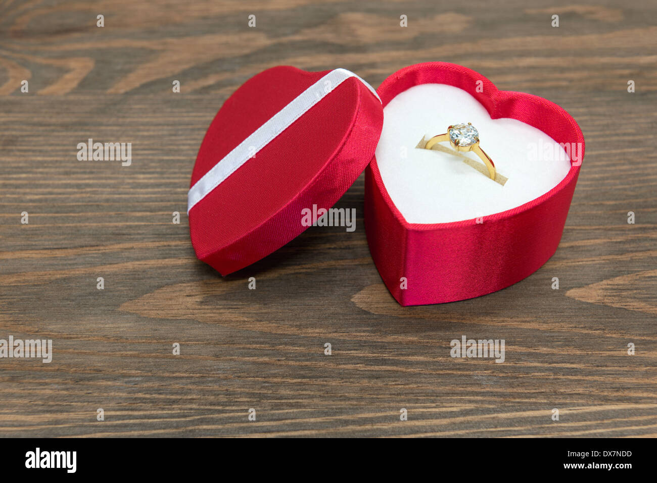 Diamond engagement ring in a red silk heart shaped box. - Stock Image
