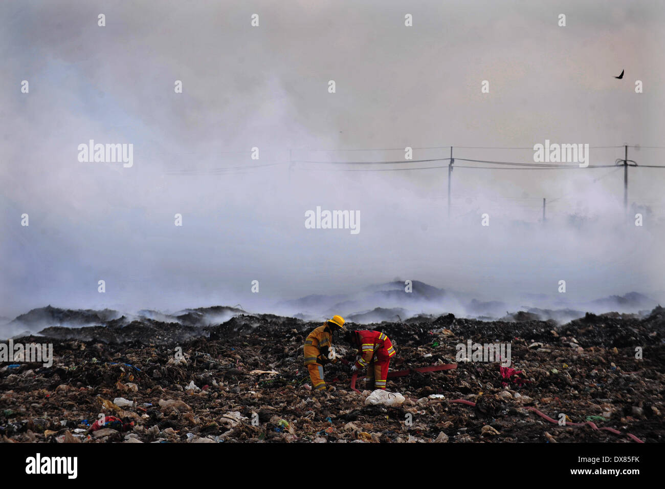 Samut Prakan, Thailand. 20th Mar, 2014. Firefighters put out a massive fire at a garbage disposal site in Samut Prakan province, Thailand, March 20, 2014. A fire started in Samut Prakan province of Thailand on March 16 and released toxic gas into the air. People living near the burning garbage dump have been forced to take shelter outside the danger zone. Credit:  Rachen Sageamsak/Xinhua/Alamy Live News - Stock Image
