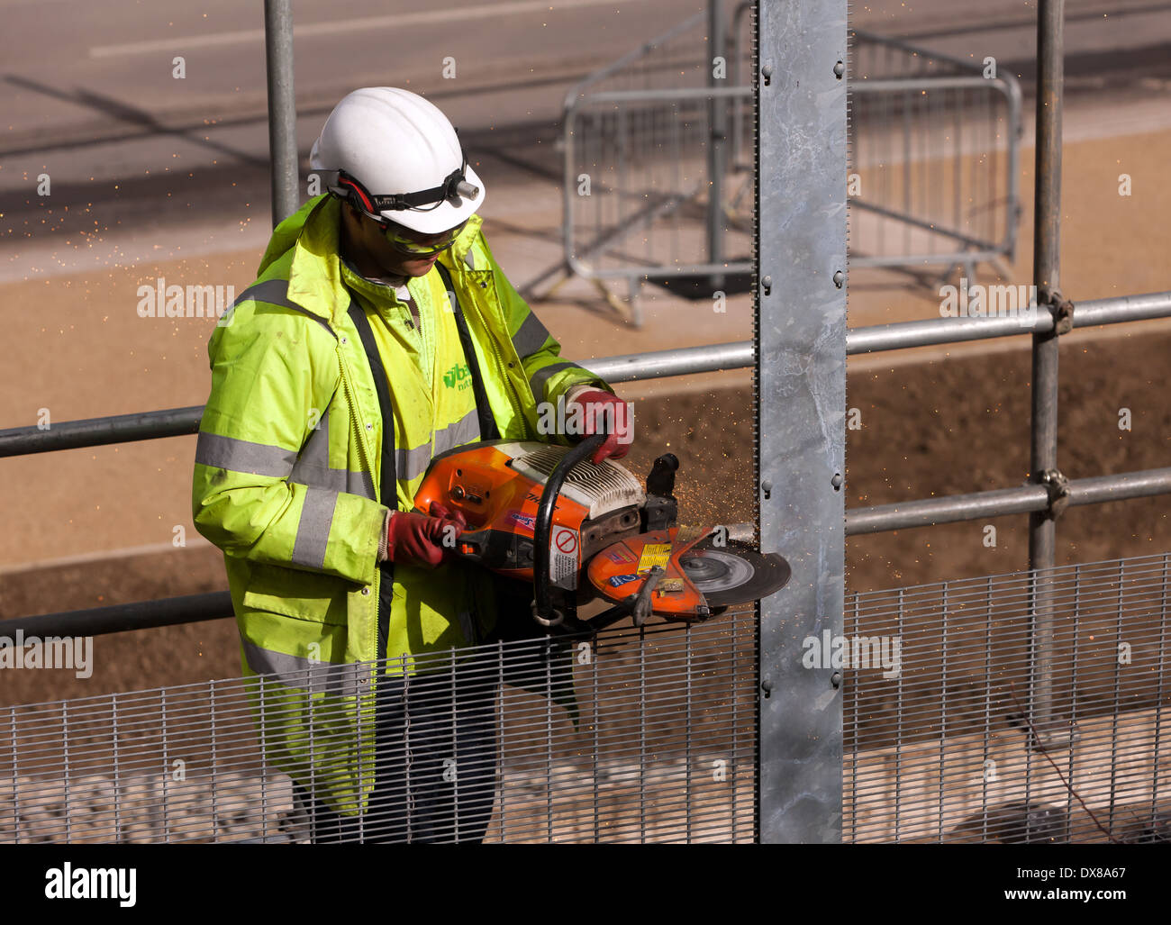 Workman using an angle -grinder to cut throughsome metal fencing at the Queen Elizabeth Olympic Park,  Stratford, London. - Stock Image