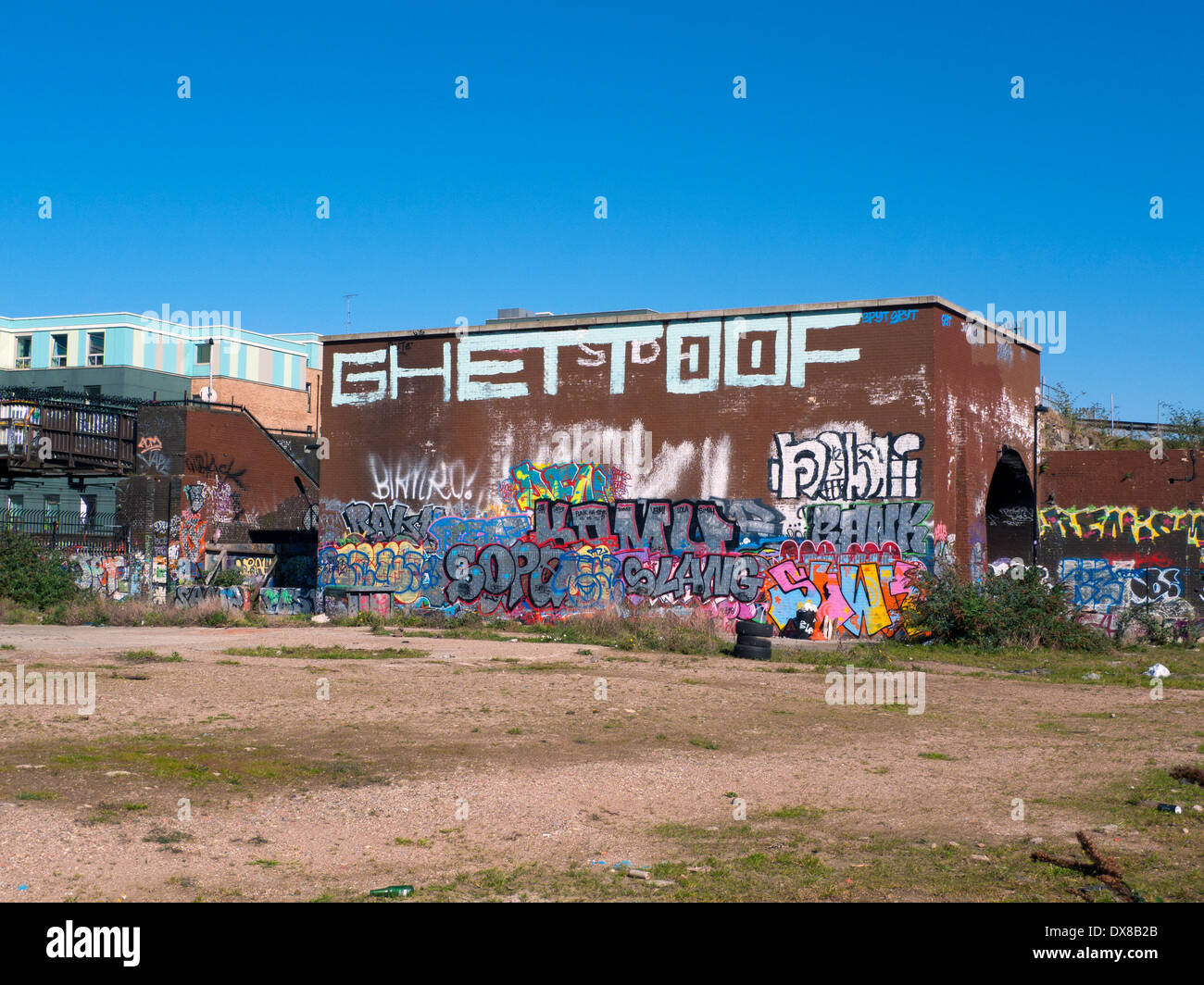 Graffiti on the side of a building bordering wasteland near Pedley Street Brick Lane E1 London UK KATHY DEWITT - Stock Image