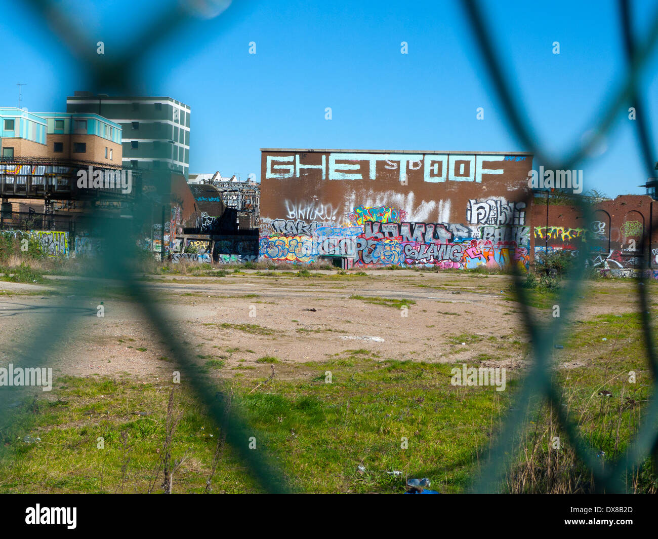 Graffiti on the side of a building viewed through fence by wasteland by Pedley Street Brick Lane E1 London UK KATHY DEWITT - Stock Image