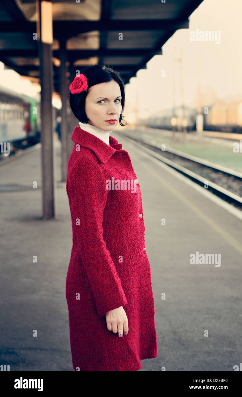 Portrait of a mid adult woman standing on railroad station platform - Stock Image