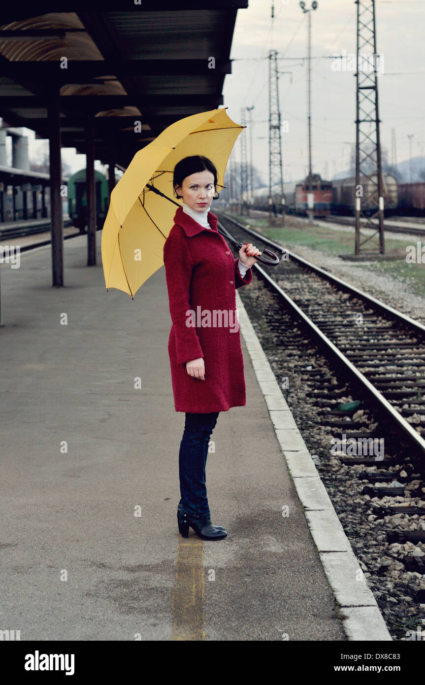 Mid adult woman standing on railroad station platform holding umbrella - Stock Image
