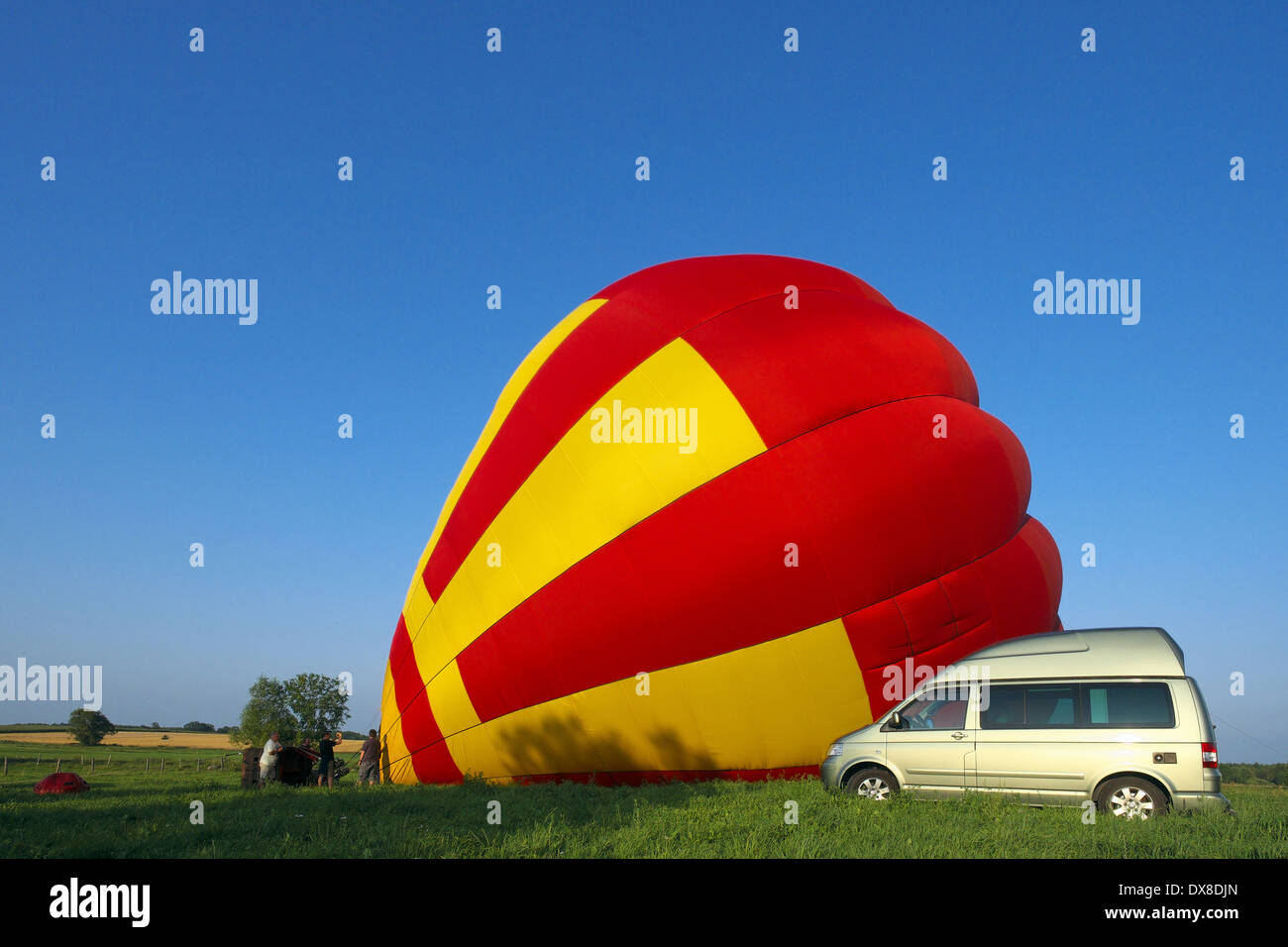 VW Volkswagen California camper next to colorful hot air balloon with people deploying it. Biebrza river National Park, Poland, - Stock Image