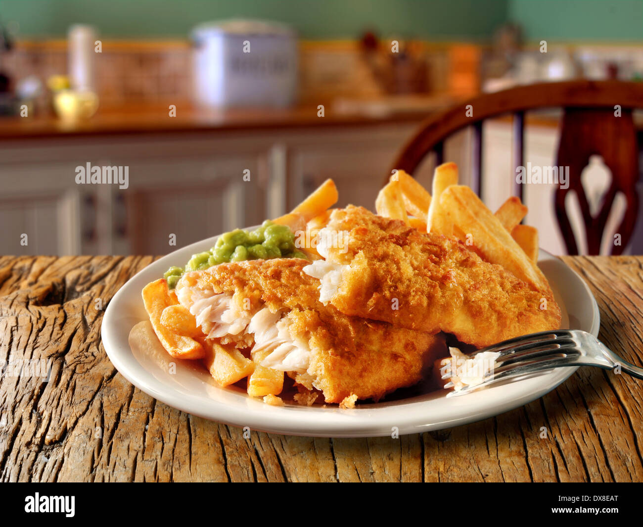 Traditional British  Battered Fish And Chips served on a plate in a traditional kitchen setting ready to eat - Stock Image