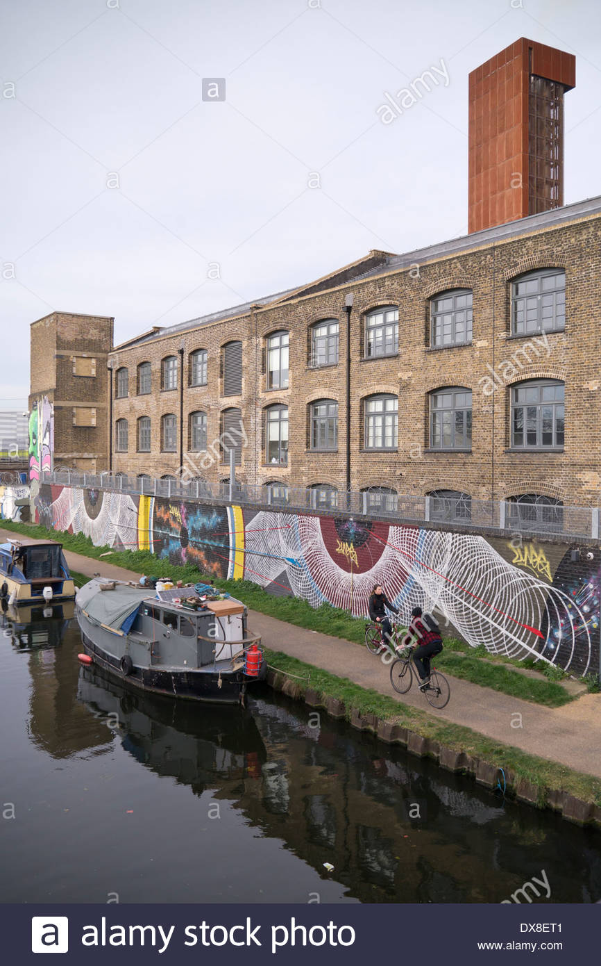 Hackney Cut towpath and painted wall art on the rear elevation of Kings Yard: Hackney Wick, London. - Stock Image