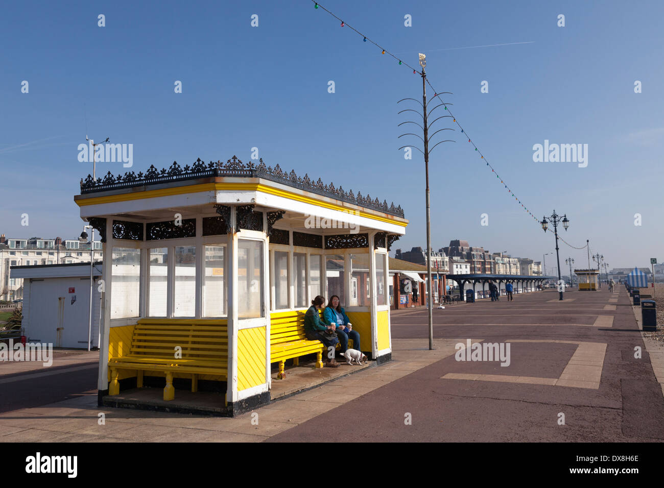 People resting in a promenade shelter at Southsea. - Stock Image