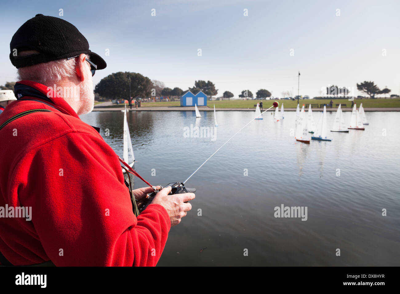 Radio controlled model yacht enthusiasts racing on Canoe Lake Southsea. - Stock Image
