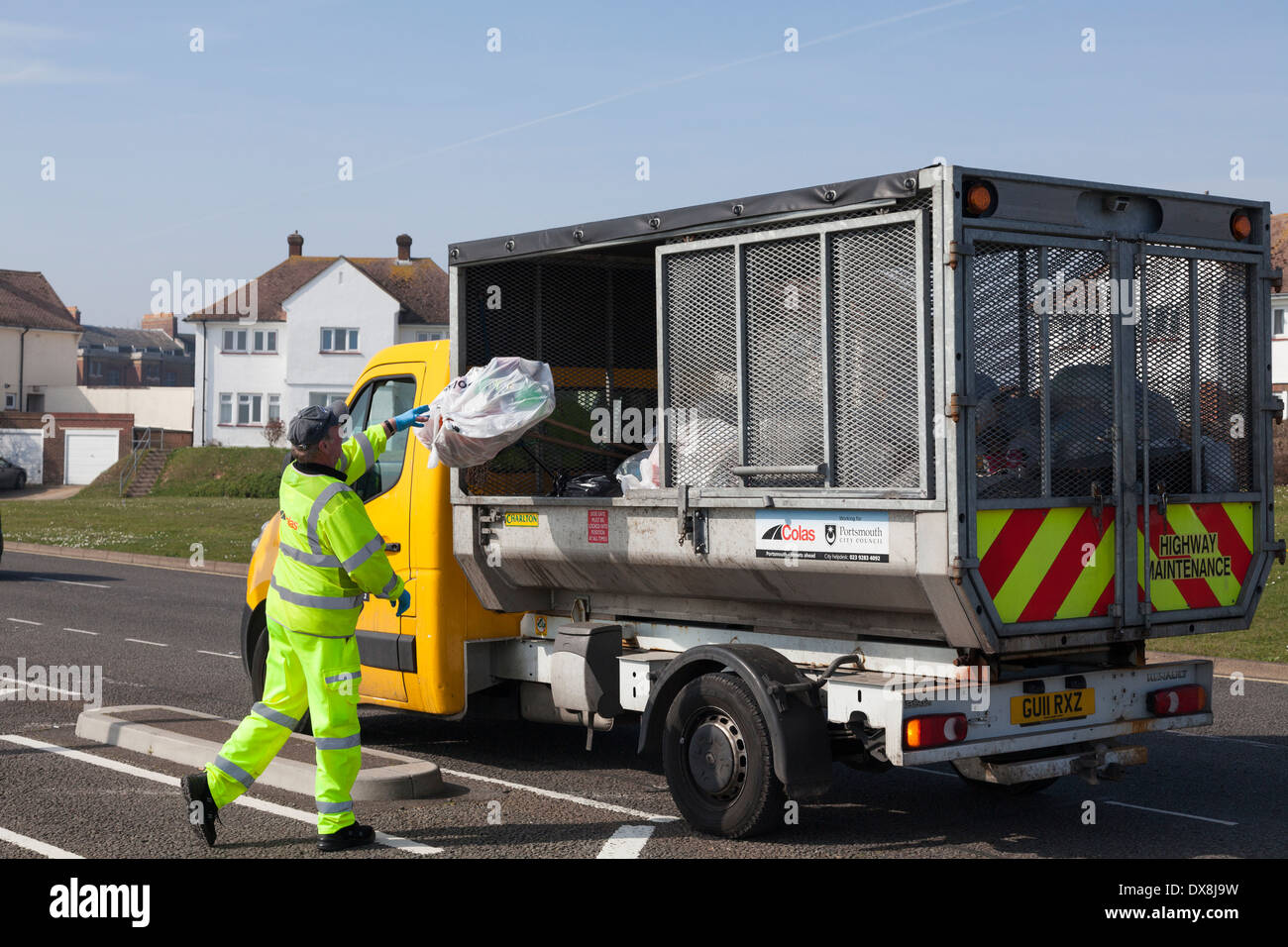 Council worker in high visibility clothing throwing rubbish into small refuse collection truck. - Stock Image